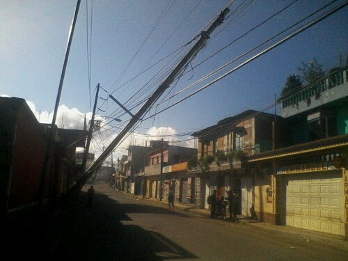 Photo of a slanted street post in a Guatemalan neighborhood